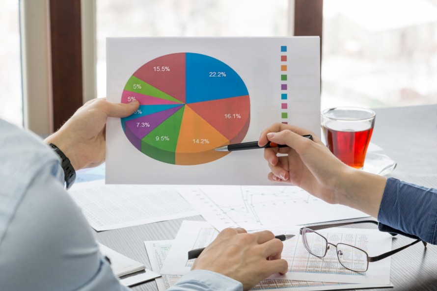 pie-chart-in-the-hands-of-young-people-closeup-ZZJBZTM